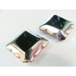 kosočtverec, barva černá, obvod a část plošky zdoben stříbrným kovem